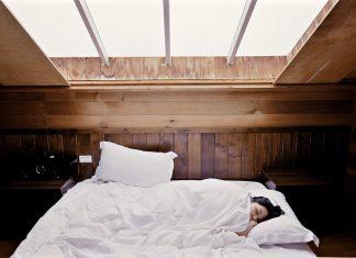 Femme qui dort sous une fenêtre avec l'apnée du sommeil.